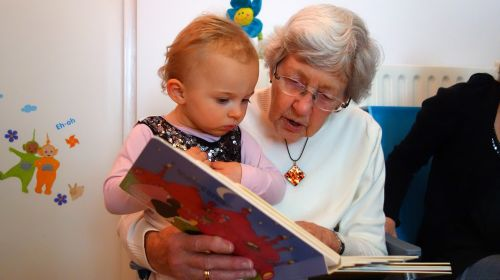 a-grandmother-reading-a-story-to-a-babygirl